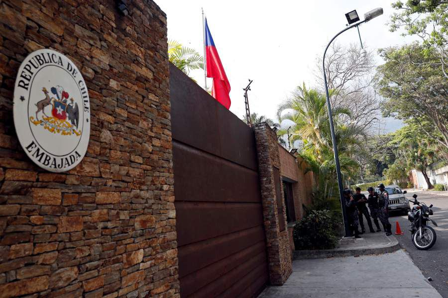 Police officers stand outside the residence of the Chilean ambassador in Caracas