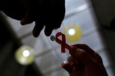 FILE PHOTO: Nurse gives a red ribbon to a woman to mark World Aids Day at the entrance of Emilio Ribas Hospital, in Sao Paulo