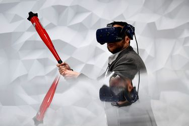 A visitor plays virtual baseball with the Vive Pro Eye virtual realit