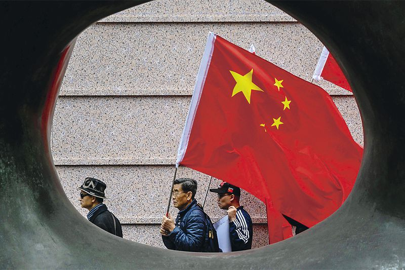 Activists shout slogans while holding China's flag as they gather outside the building that houses the Japanese embassy in Hong Kong on December 13, 2018, to mark 81 years since the 1937 Nanjing massacre. China says 300,000 people died in a six-week spree of killing, rape and destruction by the Japanese military that began in December 1937 after invading troops seized the city of Nanjing. Some respected foreign academics estimate a lower number of victims, but mainstream scholarship does not question that a massacre took place. / AFP / ANTHONY WALLACE   HONG KONG-CHINA-JAPAN-HISTORY-WWII-NANJING-WAR