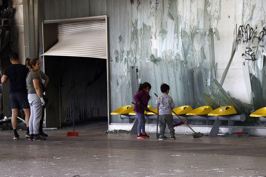 20 de Octubre de 2019.  Una familia junto a sus hijos limpia los destrozos en la estación Del Sol en Maipú, luego de que una turba la destruyera. Foto: Mario Dávila / AgenciaUno.