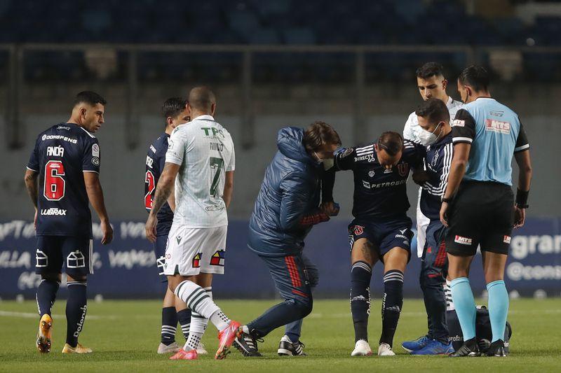 Marcelo Cañete recibe ayuda para dejar el campo de juego en el duelo entre la Universidad de Chile y Santiago Wanderers. FOTO: Agencia Uno.
