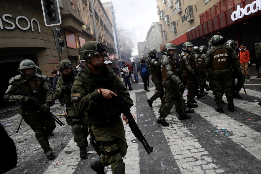Riot policemen patrol during a protest against Chile's state economic model in Concepcion