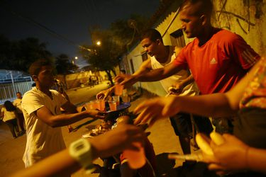 A group of Venezuelans receive help from an evangelical church along a street on the outskirts of Cucuta