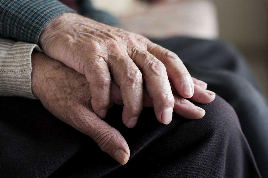 la foto muestra manos entrelazadas de adultos mayores