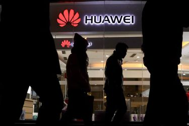 Pedestrians walk past a Huawei retail shop in Beijing Thursday, Dec.