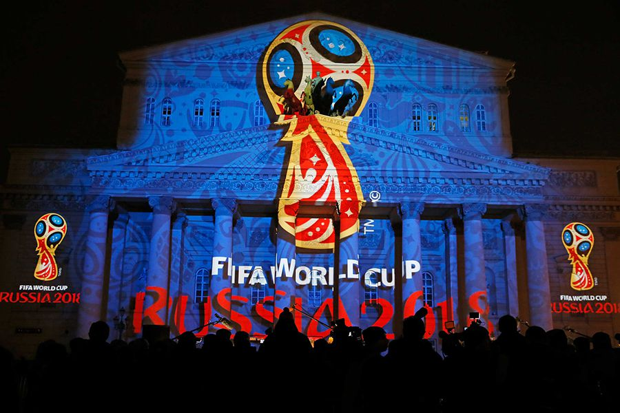 Journalists look at a light installation showing the official logotype of the 2018 FIFA World Cup during its unveiling ceremony at the Bolshoi Theater building in Moscow
