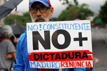 An opposition supporter holds a placard during a protest against Venezuela's President Nicolas Maduro's government in Caracas