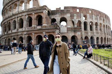 La imagen muestra a una turista frente al Coliseo Romano, usando una mascarilla para evitar la infección