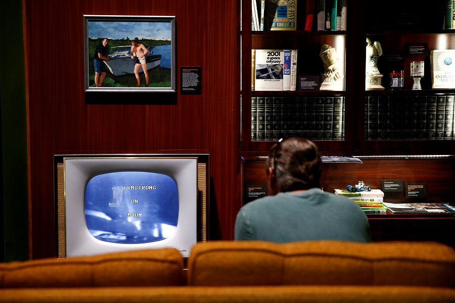"A visitor watches footage from the moon landing in a recreated 1960s-style living room at the ""Destination Moon: The Apollo 11 Mission"" exhibit at the Museum of Flight in Seattle"