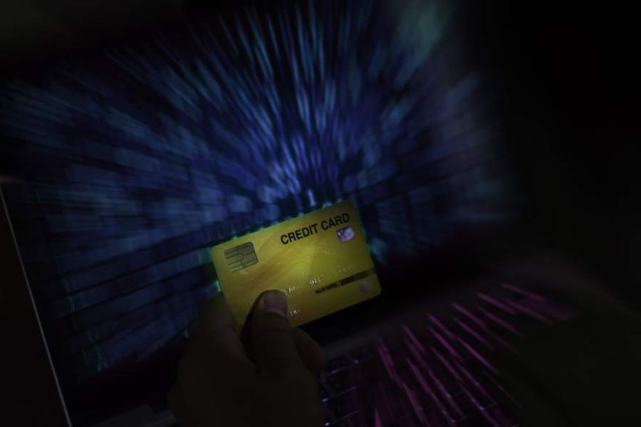 Man hand on check credit card with laptop, shopping online concept,  Dangers of using credit cards in e-commerce businesses