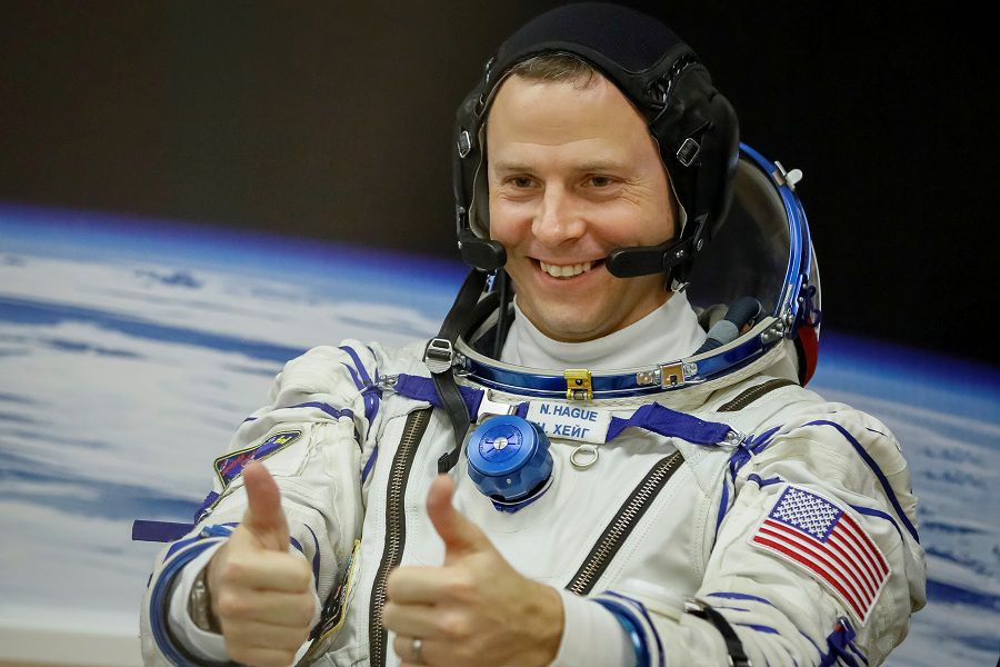 FILE PHOTO: The International Space Station (ISS) crew member Nick Hague of the U.S. gestures after donning space suits shortly before launch at the Baikonur Cosmodrome