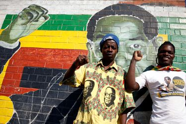 Youths stand besides a mural depicting Zimbabwe's former President Robert Mugabe after hearing the news of his death, in Mbare in the capital Harare