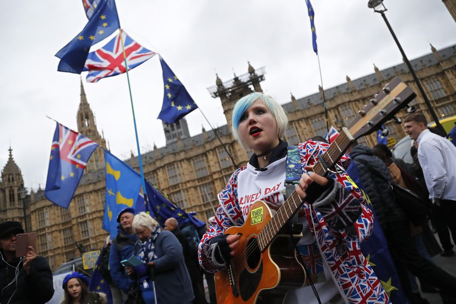 A pro-European demonstrator sings during a protest opposite the House