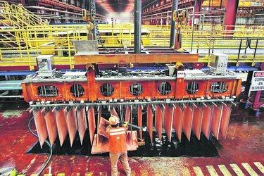 Miner checks copper cathodes at copper cathodes plant inside La Escondida copper mine near Antofagasta