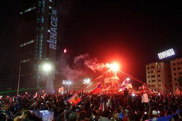 Tras triunfo del Apruebo, manifestantes ondean banderas y lanzan fuegos artificiales en una repleta Plaza Baquedano