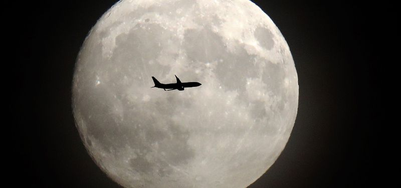 A commerical jet flies in front of the moon on its approach to Heathr