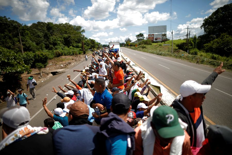 A caravan of migrants trying to reach the United States hitchhike on a truck along the highway in Tapachula