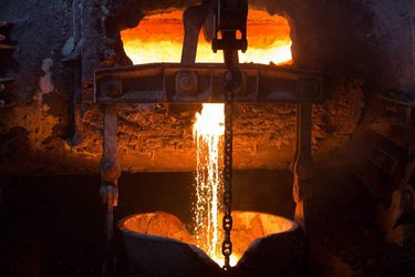Molten liquid copper is poured from a furnace at a copper refinery