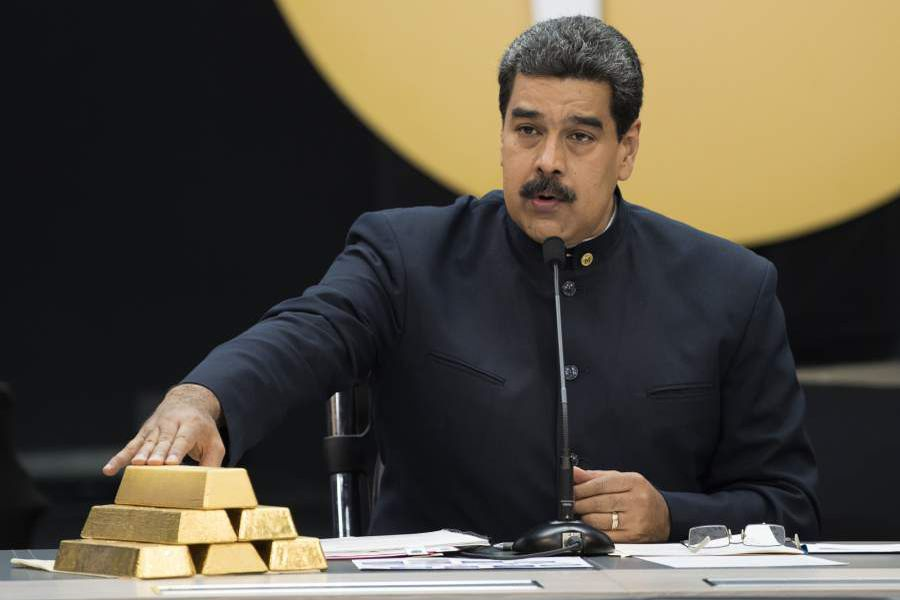 Nicolas Maduro, Venezuela's president touch a pile of 12 Kilogram gold ingots during a press conference on 'Petro' cryptocurrency in Caracas, Venezuela, on Thursday, March 22, 2018. U.S. President Trump banned U.S. purchases of 'Petro' cryptocurrency as part of a campaign to pressure the government of President Nicolas Maduro. Photographer: Carlos Becerra/Bloomberg