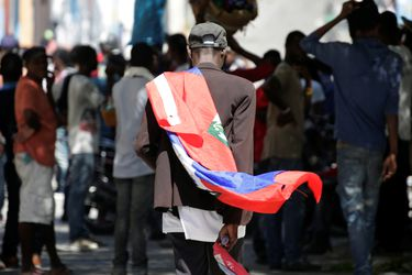 A man carrying a Haitian flag walks after a protest to demand the resignation of Haitian President Jovenel Moise, in the streets of Port-au-Prince
