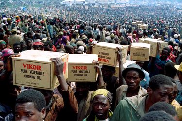 FILE PHOTO: Rwandan refugees carry food supplies away from a distribution point after the food was given out from the Red Cross