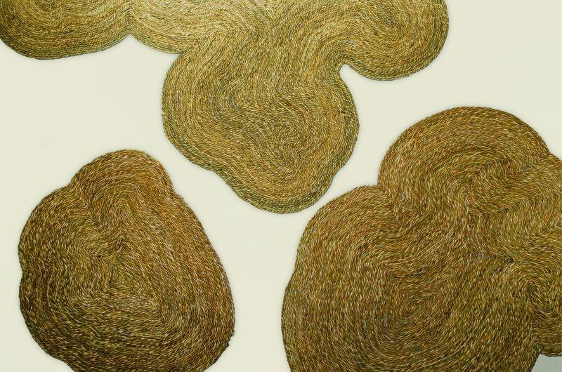 """Lagunas Lateral Diseño / 2015 ¿Te ha pasado que cuando vas en avión y miras la tierra desde arriba, los cultivos, los cerros, todo parece un gran tejido? Cuadraditos verdes, parcelas como patchwork floridos; cordones azules serpenteantes, los ríos. Y como orificios que se asoman entre la tierra, los lagos serenos. El estudio uruguayo Lateral Diseño y su trabajo Lagunas nos trae esas visiones. Esta serie de alfombras que también pueden utilizarse como paneles decorativos para la pared reproducen las siluetas de las lagunas. """"El proyecto nace del vínculo personal y emotivo con los lugares que tomamos de inspiración. Ambos integrantes del proyecto solemos vacacionar en la costa uruguaya, especialmente en Rocha; las lagunas son paraísos naturales que visitamos y donde conectamos con la naturaleza y quisimos desarrollar un producto que tradujera varios aspectos de esa experiencia"""", explica Mauro Cammá, que junto a Santiago Pittamiglio forma Lateral Diseño. Así nacen Negra, Castillos, Garzón y Rocha. Son los nombres de estas piezas que han sido tejidas a mano con materiales de esos lugares, totora, cardo, y hechas 100% a mano por artesanos locales: entre 30 y 120 horas de trabajo por cada modelo. Esta dedicación y diseño se traducen en un objeto muy hygge: cálido en sus formas orgánicas y con el tremendo regalo sensorial del tejido, que busca incansable el confín de la silueta, como hacen las ondas de agua persiguiendo la orilla de su laguna.  + lateral.com.uy"""