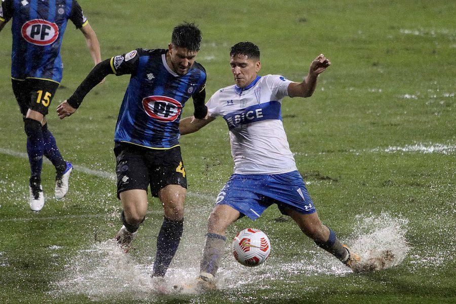 Gazzolo y Montes disputan el balón en el barrial en que se transformó la cancha del estadio CAP