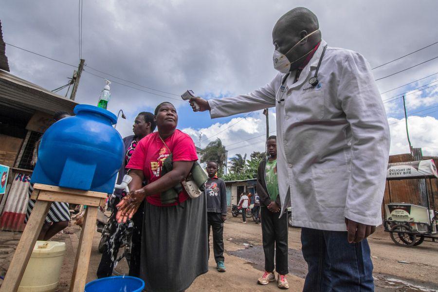 Doctor toma temperatura de personas que se lavan las manos en una estación pública de lavado de manos, como una de las medidas para prevenir el coronavirus.