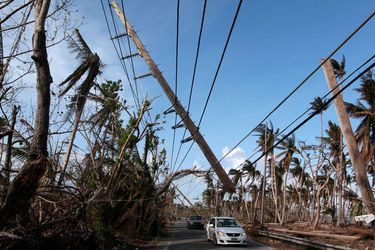 FILE PHOTO: Cars drive under a partially collapsed utility pole, after the island was hit by Hurricane Maria in September, in Naguabo