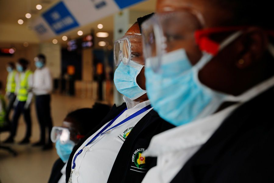 Health workers wait to screen travellers for signs of the coronavirus at the Kotoka International Airport in Accra