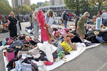 People going through piles of clothes looking for bargains at a boot sale in South london