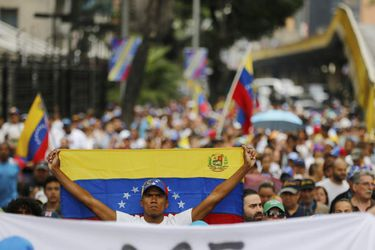 An opposition member holds a Venezuelan national flag during a protes