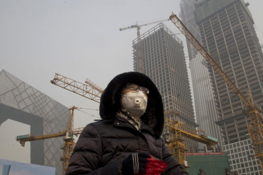 A woman wears a mask as she walks past a construction site as smog co