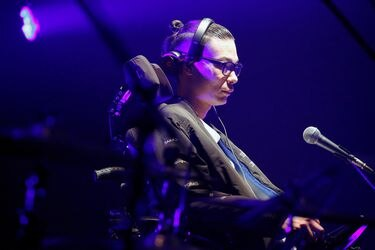 DJ Masatane Muto, diagnosed with the amyotrophic lateral sclerosis (ALS), mixes music using a smart eyewear called 'Jins Meme' which detects eye and head movements, during his performance on the stage in Tokyo