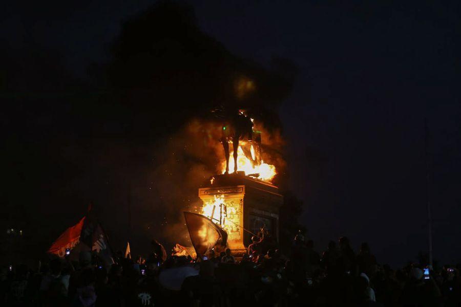 El momento de la quema del monumento de Baquedano.
