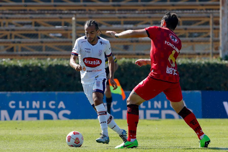 Mathías Vidangossy deja en el camino a Fabricio Fontanini, durante el partido valido por la Segunda fecha del Campeonato Nacional AFP PlanVital 2021, entre Deportes Melipilla vs Ñublense, disputado en el Estadio Municipal de la Pintana.
