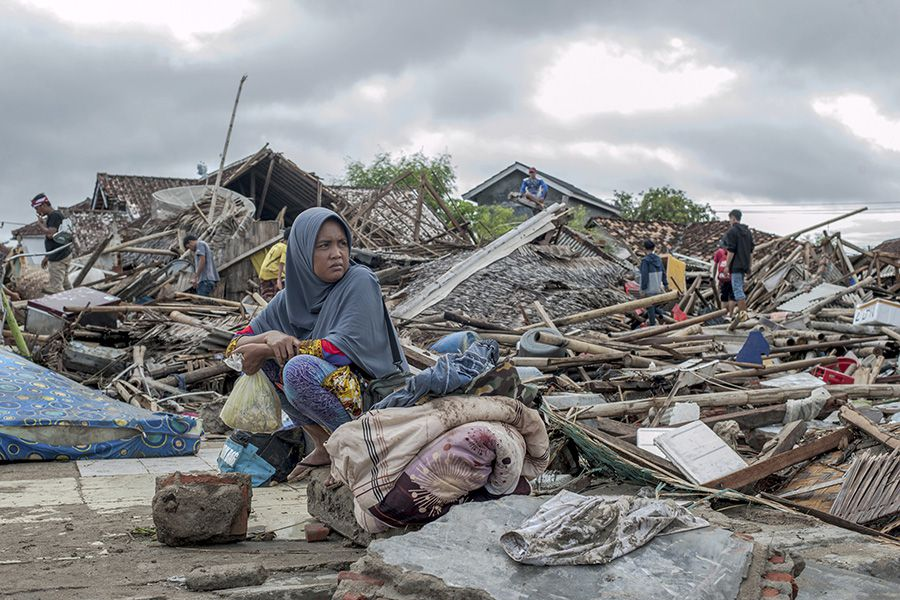 A tsunami survivor sits on a pice of debris as she salvages items fro