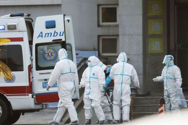 Un grupo de enfermeros lleva a una persona con coronavirus