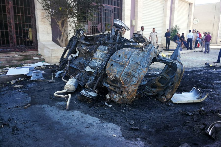 People gather at the site where a car bomb exploded in Benghazi