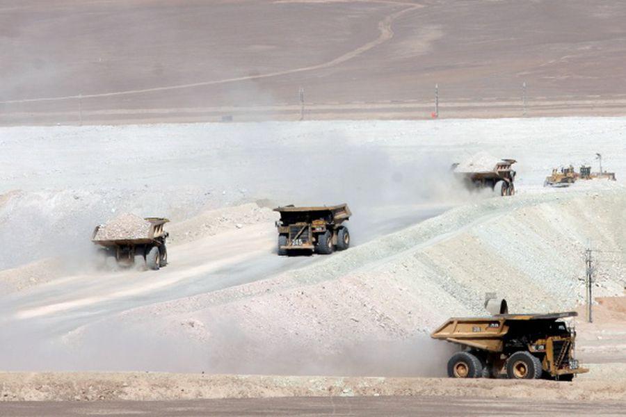 FILE PHOTO - Trucks travel along a road at Escondida, the world's biggest copper mine, in Antofagasta,