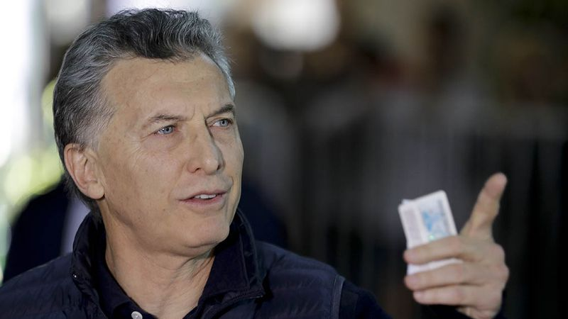 Argentina's President Mauricio Macri holds his ID after casting his v