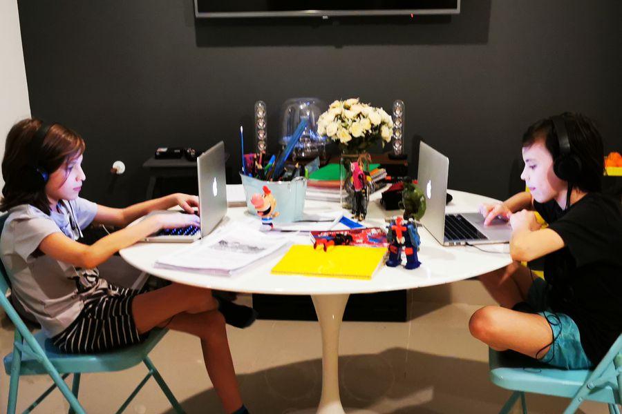 Niños que estudian en colegio virtual.