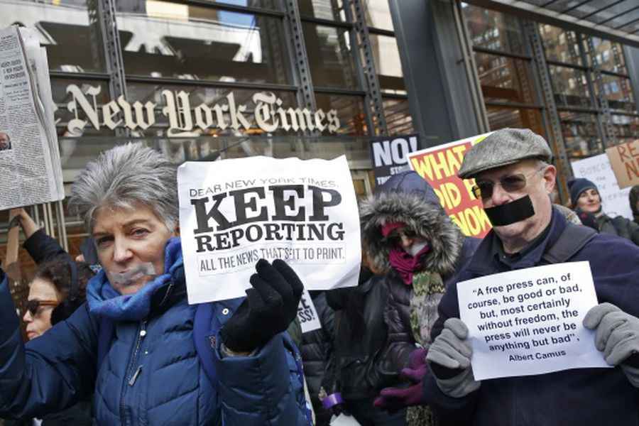 People with taped mouths hold signs and a copy of the New York Times