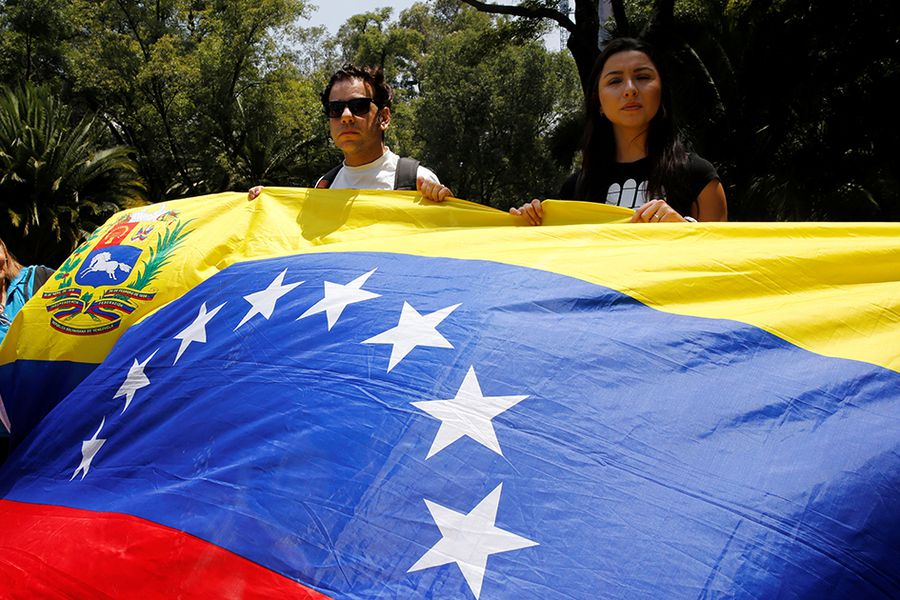 Franco Tintori holds a Venezuelan flag during a protest held by Venezuelans in Mexico against Venezuela's Constituent Assembly election, at the Heroic Children monument in Mexico City