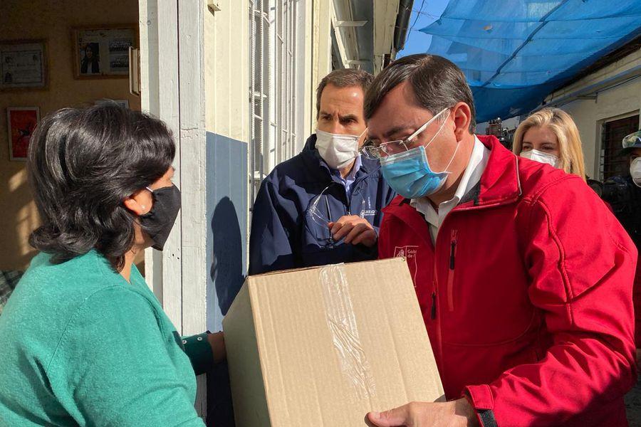 Felipe Guevara y Felipe Alessandri entregan una caja de mercadería del Gobierno.