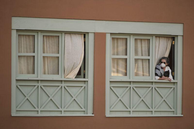 una mujer encerrada y mirando la ventana